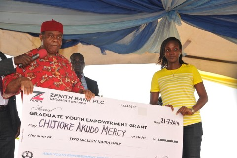 Abia state governor, Theodore Orji presenting cheques to some of the beneficiaries as part of their empowerment during the 2014 youth empowerment programme for Arochukwu, Ohafia and Bende at Bende Local Government headquaters in Bende LGA