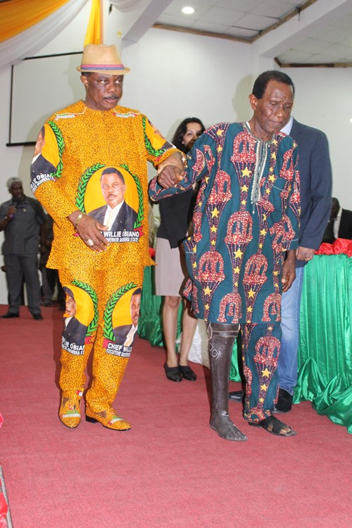 Anambra State Governor, Chief Willie Obiano helping one of the beneficiaries take the first step with the new prosthetic leg during the first phase of the programme sponsored by his wife in December 2014.