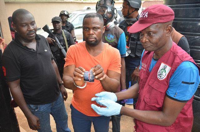 the suspect in the middle with ndlea officers during a   field test of the meth
