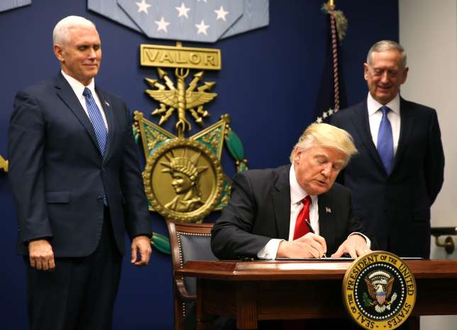 U.S. President Donald Trump (C) signs an Executive Order establishing extreme vetting of people coming to the United States after attending a swearing-in ceremony for Defense Secretary James Mattis (R) with Vice President Mike Pence at the Pentagon in Washington, U.S., January 27, 2017.