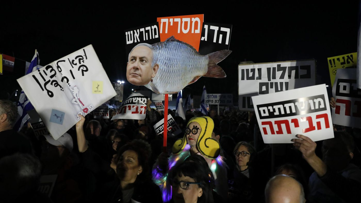 "Israeli protesters hold signs in Hebrew reading, ""The fish stinks from the head,"" on Jan. 13, 2018, during a weekly protest in Tel Aviv against government corruption."