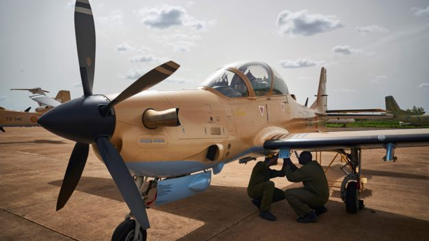 Two mechanics prearrange one of the four newly arrived turboprop light attack aircrafts 'Super Tucano' at the military air base in Bamako on July 11, 2018.