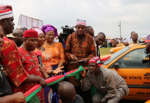 Abia state governor, Theodore Orji cutting the tape to commission the 200 vehicles procured for the 2014 youth empowerment programme of Arochukwu, Ohafia and Bende at Bende Local Government headquaters in Bende LGA.with him from L-R are Rt.Hon. Ude Okochukwu, speaker, Abia state house of assembly, Lady Mercy Orji wife of the governor and Lady Nene Ananaba wife of the deputy governor.