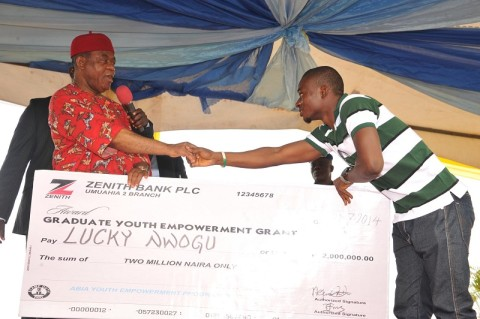 Abia state governor, Theodore Orji presenting cheques to some of the beneficiaries as part of their empowerment during the 2014 youth empowerment programme for Arochukwu, Ohafia and Bende at Bende Local Government headquaters in Bende LGA.
