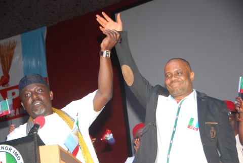 Gov Rochas Okorocha as he raises the hands of Dr Hilary Eke, State Chairman, APC during the inauguration ceremonies at Imo International Convention Center, Owerri recently