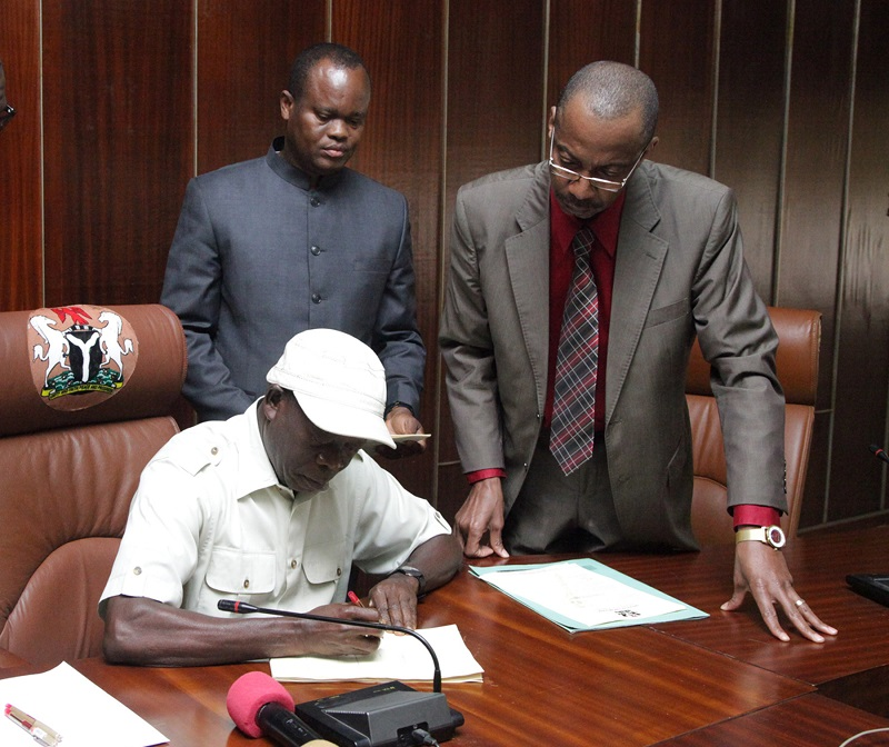 Governor Adams Eric Oshiomhole signs the Edo State 2015 Appropriation Bill into Law watched by the Commissioner for Budget and Economic Planning, Hon Lawrence Aghedo (2nd right) and Rt Hon Uyi Igbe, Speaker, Edo State House of Assembly (right).