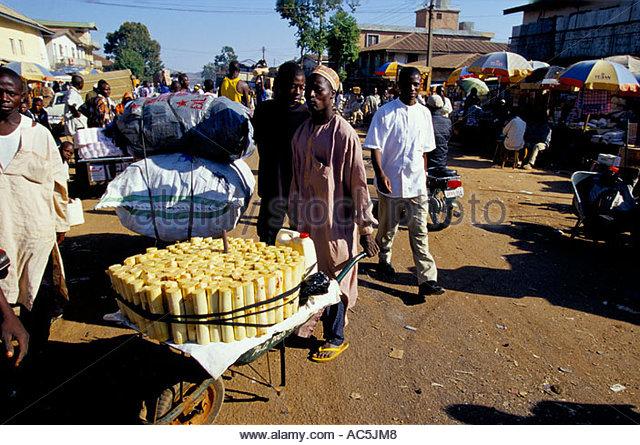 man-with-wheelbarrow-full-of-chopped-wood-in-lagos-market-nigeria-ac5jm8